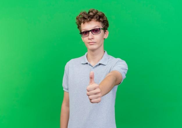 Junger mann in der schwarzen brille, die graues poloshirt trägt, das hapy und positiv lächelnd daumen über grün zeigt