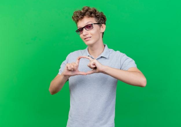 Junger mann in der schwarzen brille, die graues poloshirt trägt, das herzgeste mit den fingern macht, die glücklich und positiv lächelnd über grüner wand lächeln