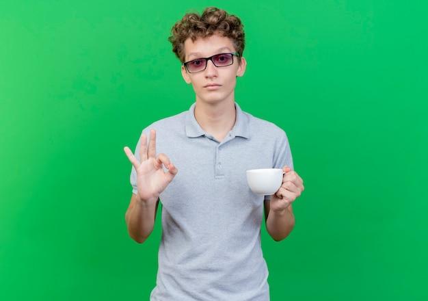 Junger mann in der schwarzen brille, die graues poloshirt trägt, das kaffeetasse glücklich und positiv zeigt ok zeichen, das über grüner wand steht