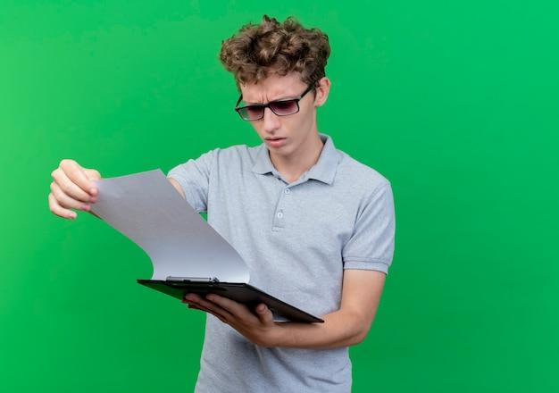 Junger mann in der schwarzen brille, die graues poloshirt trägt, das klemmbrett mit leeren seiten hält, die es mit ernstem gesicht über grün betrachten