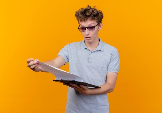 Junger mann in der schwarzen brille, die graues poloshirt trägt, das klemmbrett mit leeren seiten hält, die es über orange überrascht betrachten