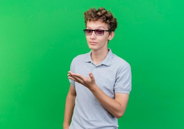 Junger mann in der schwarzen brille, die graues poloshirt trägt, das mit arm über grün gestikuliert