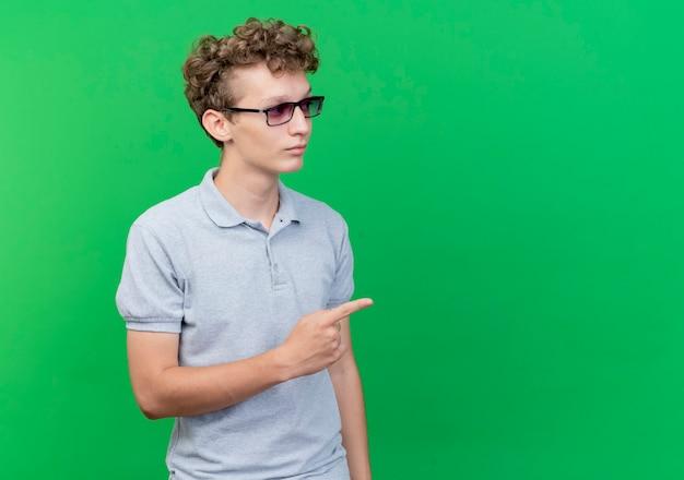 Junger mann in der schwarzen brille, die graues poloshirt trägt, das mit ernstem gesicht beiseite schaut, das mit zeigefinger auf etwas über grün zeigt