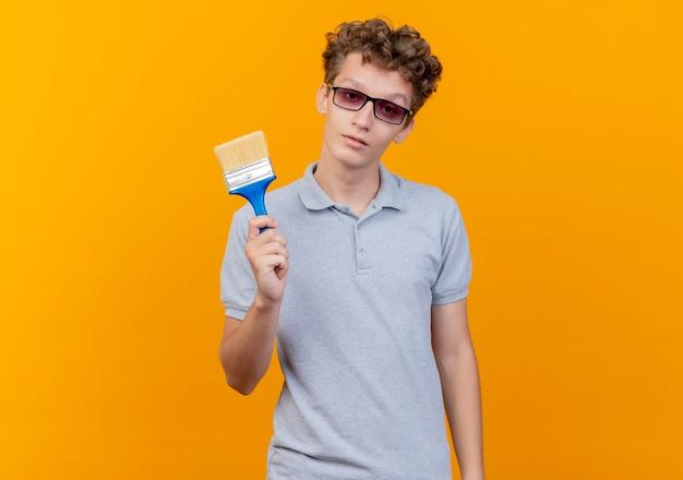 Junger mann in der schwarzen brille, die graues poloshirt trägt, das pinsel mit ernstem gesicht über orange zeigt