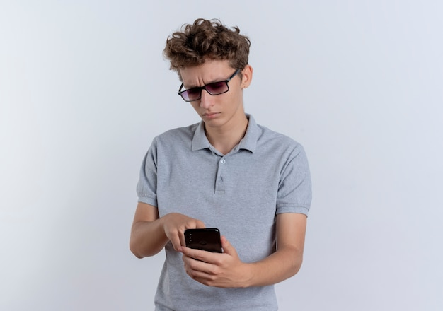 Junger mann in der schwarzen brille, die graues poloshirt trägt, das sein smartphone-handy mit ernstem gesicht betrachtet, das über weißer wand steht