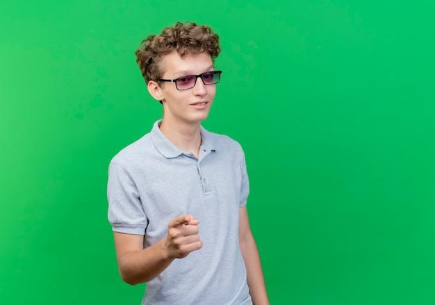Junger mann in der schwarzen brille, die graues poloshirt trägt, das sicher zeigt, mit zeigefinger auf kamera über grün zu zeigen