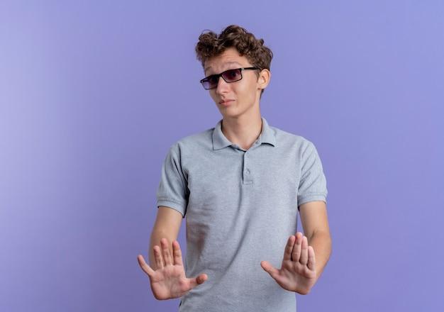 Junger mann in der schwarzen brille, die graues poloshirt trägt, das stoppschild hält, das hände heraushält, wie das erzählen nicht näher kommt, das über der blauen wand steht
