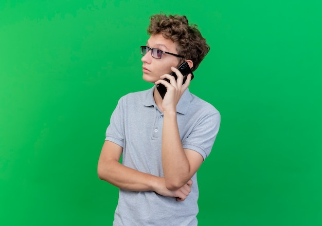 Junger mann in der schwarzen brille, die graues poloshirt trägt, das verwirrt schaut, während auf handy über grün spricht