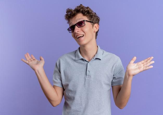 Junger mann in der schwarzen brille, die graues poloshirt trägt, das verwirrte und unsichere hände betrachtet, die keine antwort haben, die über blauer wand steht