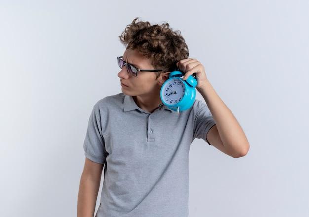 Junger mann in der schwarzen brille, die graues poloshirt trägt, das wecker nahe seinem ohr hält und versucht, über weiß zu hören