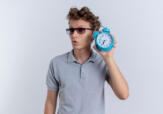 Junger mann in der schwarzen brille, die graues poloshirt trägt, das wecker zeigt, der besorgt über weiß schaut
