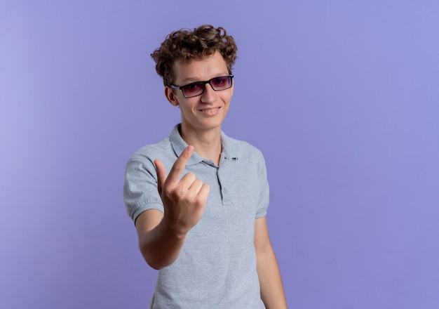 Junger mann in der schwarzen brille, die graues poloshirt trägt, kommt hierher geste mit hand, die über blauer wand steht
