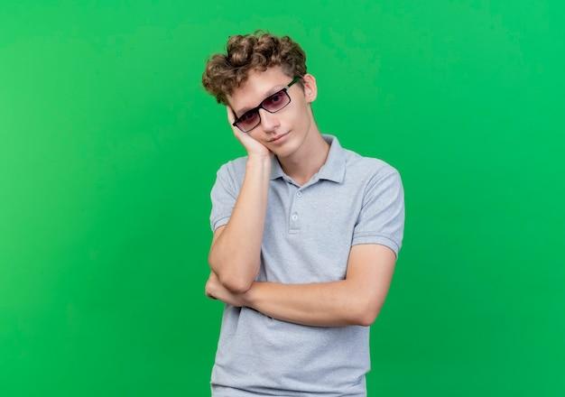Junger mann in der schwarzen brille, die graues poloshirt trägt, lehnt kopf auf seinem arm, der über grün wartet