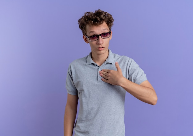 Junger mann in der schwarzen brille, die graues poloshirt trägt und auf sich selbst zeigt, verwirrt über der blauen wand stehend