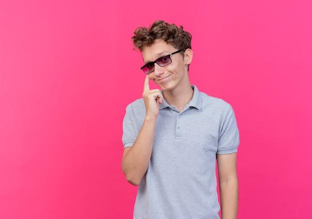 Junger mann in der schwarzen brille, die graues poloshirt trägt, zeigt sein auge lächelnd und beobachtet, wie sie über rosa gestikulieren