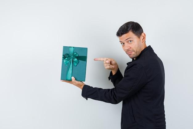 Junger mann in der schwarzen jacke, die auf geschenkbox zeigt und positiv schaut.
