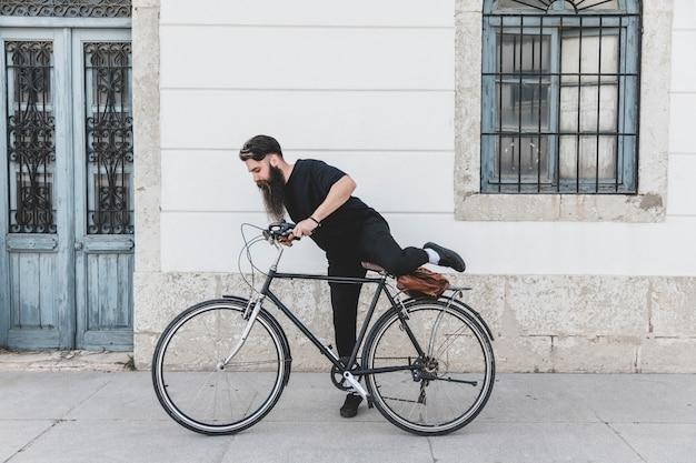 Junger mann in der schwarzen kleidung, die auf fahrrad über der straße sitzt