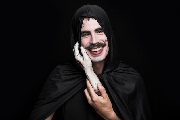 Junger mann in der schwarzen kleidung, die leichenhand und -c $ lächeln hält
