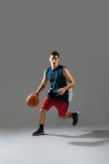 Junger mann in der sportbekleidung, die basketball spielt