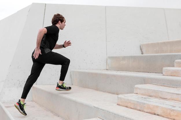 Junger mann in der sportbekleidung, die draußen trainiert