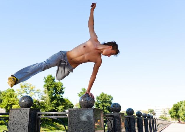 Junger mann in der sportbekleidung, die parkour draußen auf marmorzaun am klaren sommertag springt und übt
