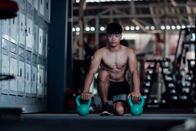 Junger mann in der sportkleidung eine übungsklasse in einer turnhalle