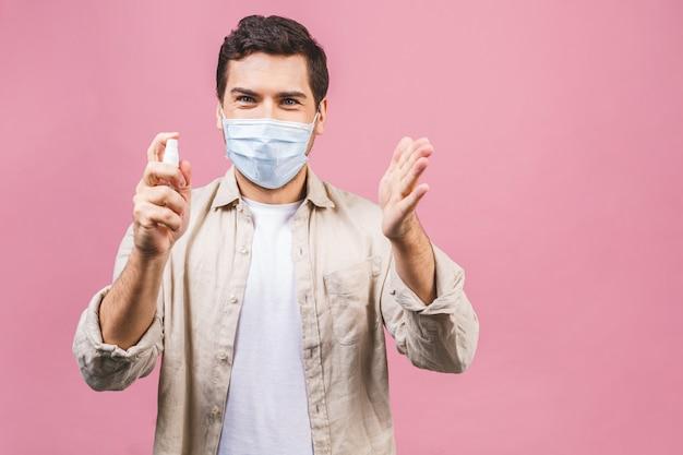 Junger mann in der sterilen gesichtsmaske isoliert. epidemisches pandemie-coronavirus 2019-ncov sars covid-19-grippevirus-konzept. flasche mit alkoholflüssigem antibakteriellem desinfektionsmittel.