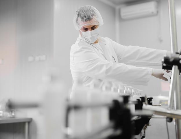 Junger mann in der sterilen kleidung, die produktionslinie von kosmetischen produkten kontrolliert