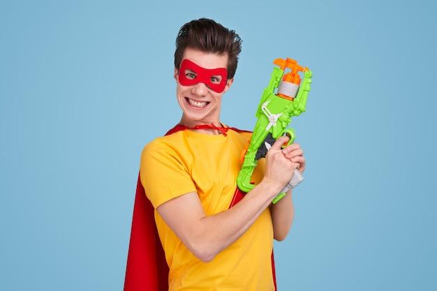 Junger mann in der superheldenmaske und im umhang, die für kamera lächeln und abzug auf spielzeugwaffe gegen blauen hintergrund ziehen