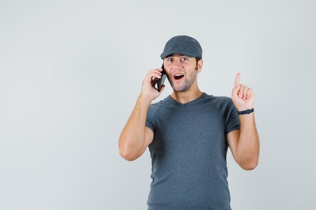 Junger mann in der t-shirt-kappe, die ausgezeichnete idee findet, während er auf handy spricht