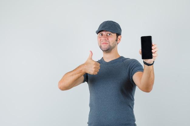 Junger mann in der t-shirt-kappe, die daumen oben zeigt, während handy hält