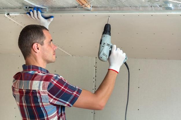 Junger mann in der üblichen kleidung und in den arbeitshandschuhen, die trockenbau verschobene decke reparieren