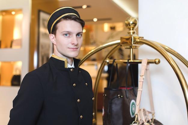 Junger mann in der uniformumhüllung im hotel