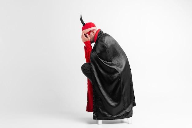 Junger mann in der verzweiflung in der maskeradekleidung und im roten hut mit den schwarzen hörnern, die sein gesicht mit hand sover weißen hintergrund bedecken.