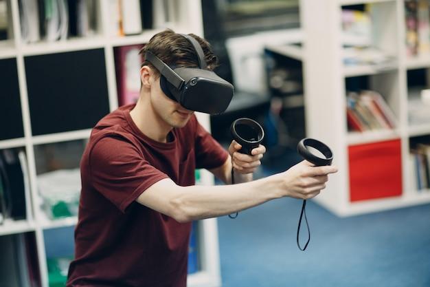 Junger mann in der virtuellen realität schutzbrille, vr brille headset mit joystick