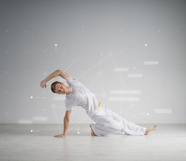 Junger mann in der weißen sportbekleidung, die einen tritt ausführt. indoor martial arts training, capoeira.