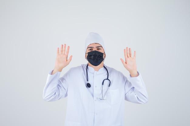 Junger mann in der weißen uniform, maske, die hände in der übergabegeste erhebt und hilflos schaut, vorderansicht.