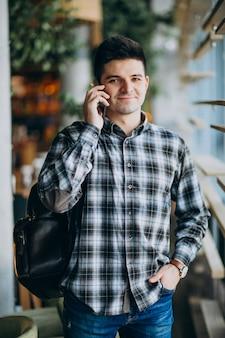 Junger mann in einem café, das das fenster bereitsteht und am telefon spricht