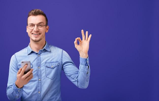 Junger mann in einem denimhemd, das an hand handy und shows ok hält