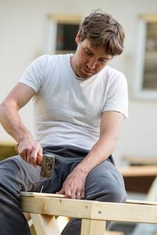 Junger mann in einem diy-projekt draußen, der beim bau eines spielhauses einen nagel in eine holzkonstruktion hämmert.