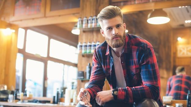 Junger mann in einem friseursalon selbstbewusster look mit frisur