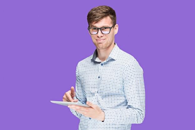 Junger mann in einem hemd, das am laptop auf lila arbeitet