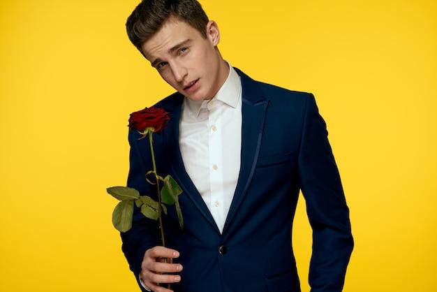 Junger mann in einem klassischen anzug mit einer rose in seinen händen, sexy blick
