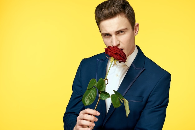 Junger mann in einem klassischen anzug mit einer roten rose in seiner hand auf einem gelben hintergrundemotionen beschnittenes ansichtsmodell. hochwertiges foto