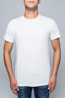 Junger mann in einem lässigen stil kleidet weißes t-shirt und blaue jeans auf weiß