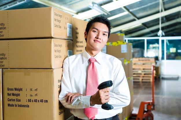 Junger mann in einem lager mit scanner