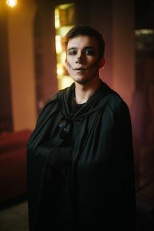Junger mann in einem schwarzen halloween-anzug schaut mit ernstem gesicht in eine kamera