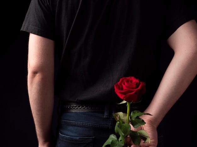 Junger mann in einem schwarzen t-shirt anzug hält eine rote rose hinter sich auf einem schwarzen hintergrund