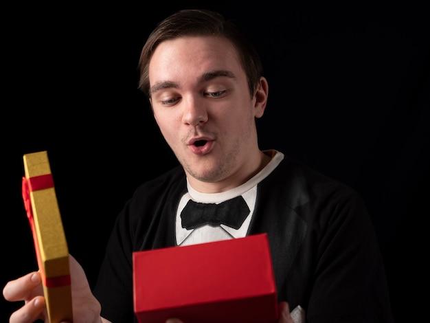 Junger mann in einem schwarzen t-shirt anzug öffnet ein gelb-rotes geschenk mit überraschung auf einem schwarzen