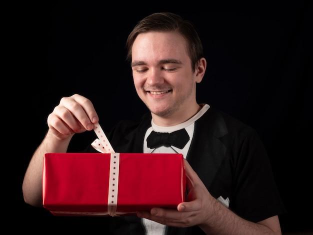 Junger mann in einem schwarzen t-shirt anzug öffnet ein rotes geschenk auf einem schwarzen hintergrund